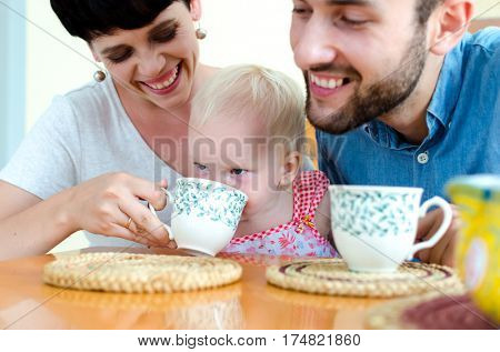 Young family at home on the weekend. Family drinking tea.