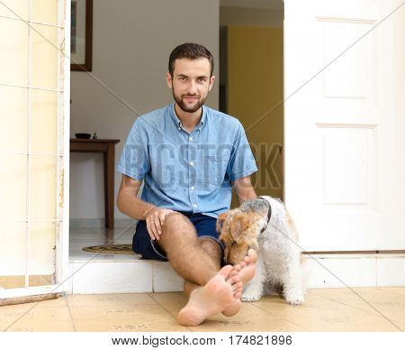 A man and a dog. Man sitting on the porch with his pet.