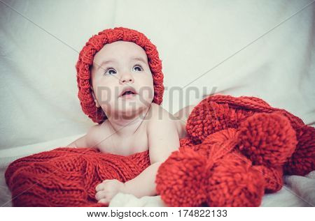 Portrait of little girl in hat. The child is wrapped in a red big scarf.