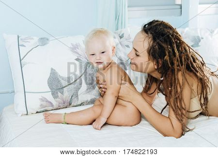 Mom and baby on the bed. A woman and her todler are playing lying in the bedroom.