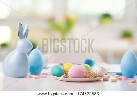 Easter decorated table with painted eggs and rabbit