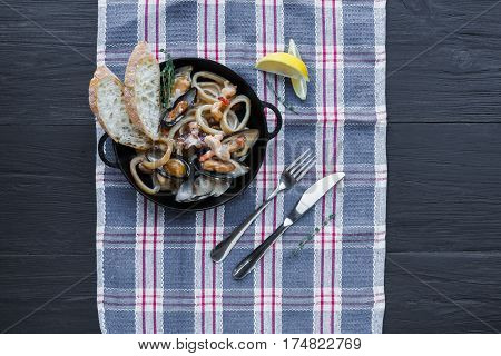 Seafood Stew in Saucepan. Authentic italian restaurant cuisine, healthy food. Oysters, shrimps, calamari in white cream with bruschetta. Bowl on napkin on dark black wood background, top view