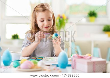 Happy pretty child girl having fun during painting eggs for Easter in spring at home