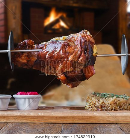 Grill dish in restaurant with fireplace. Grilled roasted pork knuckle on spit with fried sauerkraut cabbage and sauces. Juicy meat meal closeup, german food