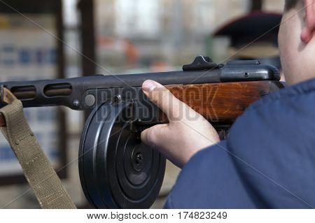 Closeup of a man pointing a retro looking machine gun outdoor cropped shot
