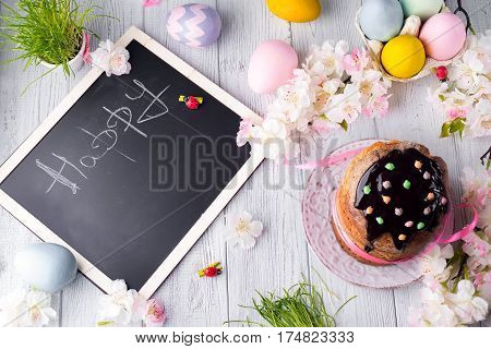 Easter cake with colored eggs and board chalk copy space on a white wooden background, top view flat lay