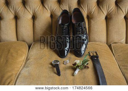 Wedding details. Groom accessories. Shoes, cufflinks, belt watch boutonniere on sofa