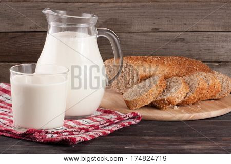 jug of milk with a loaf of bread on a wooden background.