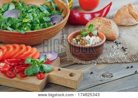 Ingredients for vegetables salad on a wooden background: lettuce leaves tomatoes red pepper onions olives oil and cheese.
