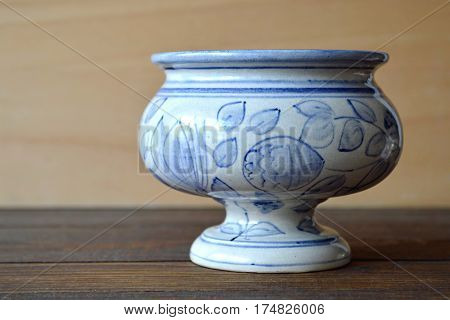 Antique porcelain apothecary jar on wooden background