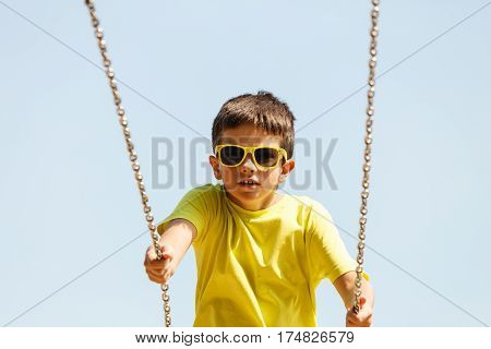 Rest and relax for children. Little boy in sunglasses resting swinging outdoor. Adorable child having fun playing in playground.