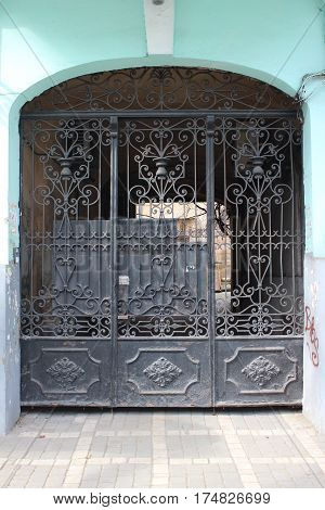 Old vintage metal entrance gate with wrought iron bars