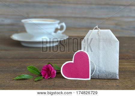 Tea bag with heart-shaped tag porcelain tea cup and rose poster
