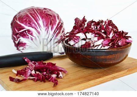 Fresh radicchio in the bowl on wooden board
