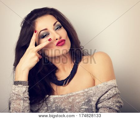 Grimacing Happy Female Model Showing Rock Gesture In Fashion Necklace. Bright Makeup And Red Lipstic