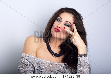 Grimacing Happy Female Model Showing Rock Gesture In Fashion Necklace On Blue Background With Empty