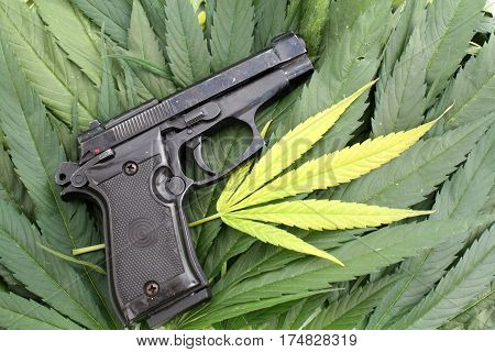 Crime illegal marijuana conceptual photo of gun and marijuana leaf