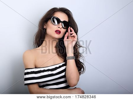 Chic Female Model With Long Hair Posing In Fashion Sunglasses In Striped Dress With Hand Near Face O