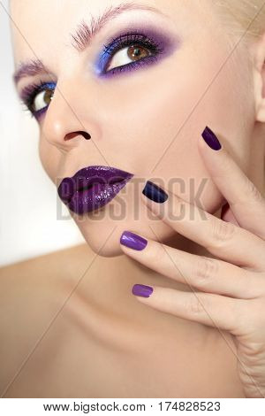 Blue purple fashion multicolored manicure and makeup on the blonde woman on gray background.