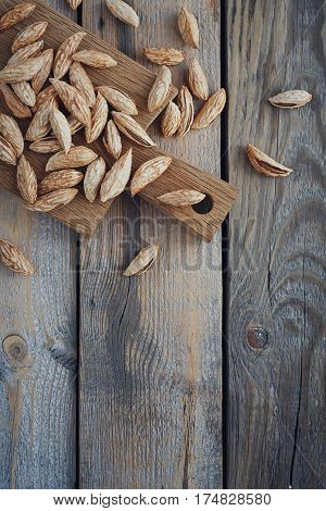 Almonds nuts on a rustic wooden background. Nuts background with copy space. Top view.