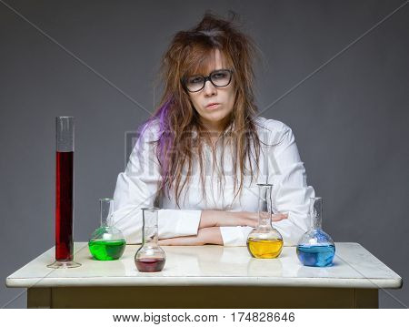 Serious messy scientist in lab on gray background