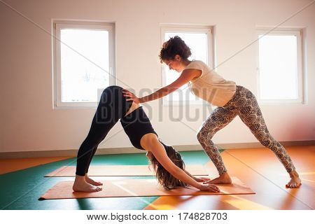 yoga instructor assisting student in exercise healthy lifestyle concept indoor shot