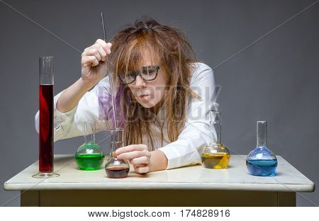 Working messy chemist in lab on gray background