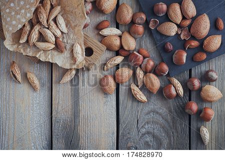 Variety of nuts: almonds mountain almonds and hazelnuts on rustic wooden background. Nuts background with copy space. Top view.