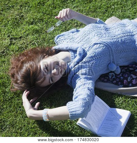 Girl student learning on the grass in the park (education self-development self-organization time management)