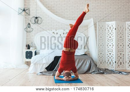 Morning in the bedroom a man stands on his head he does yoga exercises.