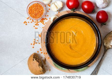 Red lentil cream soup in dark ceramic bowl on round cutting board. Grain lentils vegetables and bread. Vegetarian nutrition. Top view.