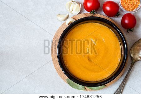 Red lentil cream soup in dark ceramic bowl on round cutting board. Grain lentils and vegetables. Vegetarian nutrition. Top view.