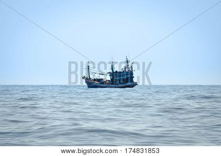 blue Fishing trawler on the ocean water alone