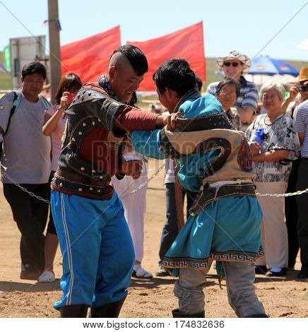 Inner Mongolia, China - Jul 14, 2011: The Mongolian Young Men Wrestling In The In The Steppe Near Ho