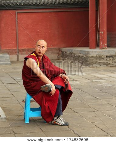 Hohhot, Inner Mongolia - Jul 12, 2011: Buddhist Monk With Rosary Sitting In The Yard Of Dazhao Monas