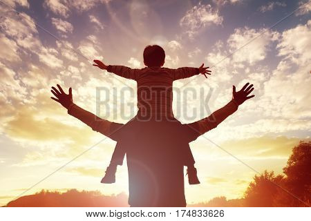 Family time father and son watch and praise the sunset