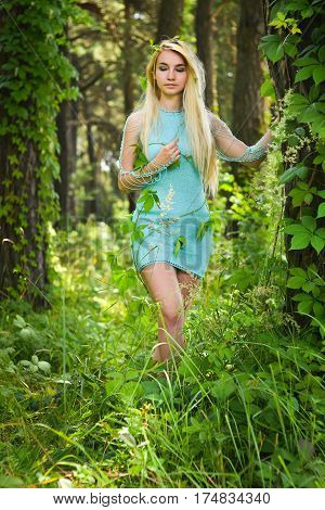 Pretty young blonde girl with closed eyes and long hair in turquoise dress standing in the green forest where trees are enlaced with lianas