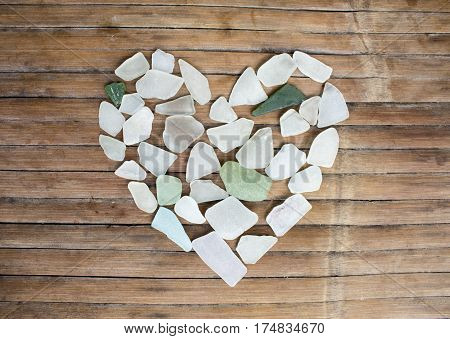 Seashore glass pebble heart on wooden background. Sugar glass mosaic for Valentine's Day. Romantic shabby chic decor. Seaside greetings for Valentine Day. Beach glass on grungy wood card template