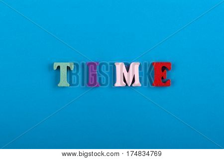 Time is running up. Time Word composed from colorful wooden letters on blue background