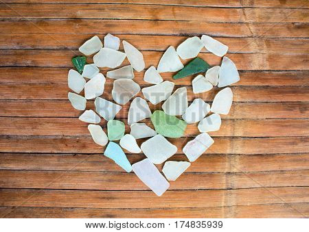 Seashore glass pebble heart on wooden background. Sugar glass mosaic for Valentine's Day. Romantic shabby chic decor. Seaside greetings for Valentine Day. Handpicked beach glass on grungy wood.