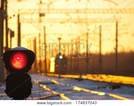 Railway traffic light shows blue signal on railway and railway with freight train as the background during sunset.