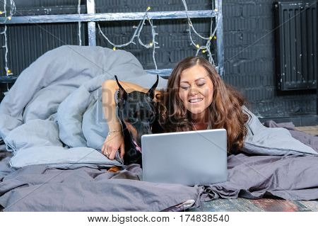 Woman in bed with big black doberman dog and laptop.