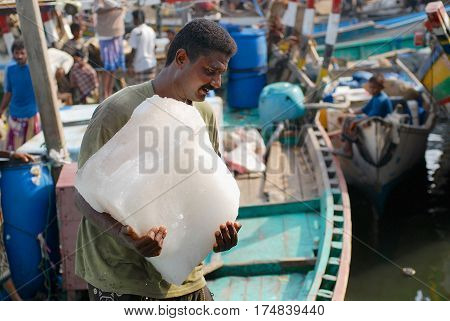 AL HUDAYDAH, YEMEN - SEPTEMBER 17, 2006: Unidentified fisherman carries pack of ice in the fishing port in Al Hudaydah, Yemen.