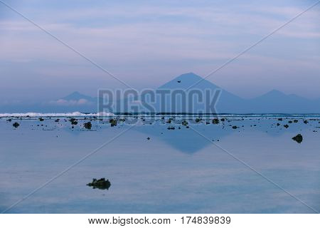 Views of the Agung volcano with reflection in the water off the island of Gili Trawangan in the early morning at low tide with exposed rocks Indonesia