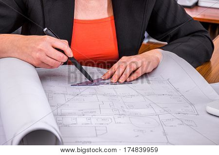 Woman engineer draws drawings. Architect at work. Close-up.