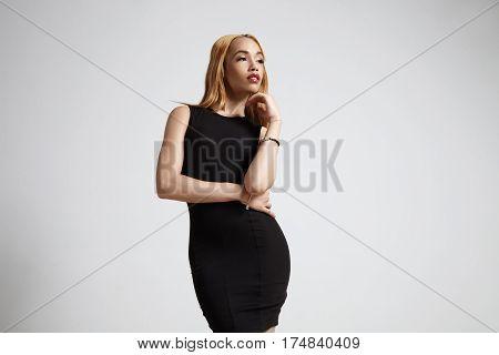 femenine delicate woman in black dress watching aside