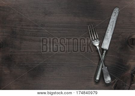 Crossed vintage silver fork and knife on the background of old brown wooden board with copy-space