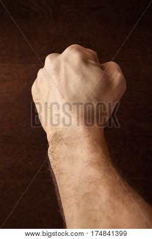 Strong Male Fist Over Dark Wooden Wall