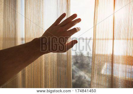 Hand Opens Tulle On Window