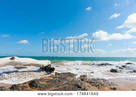 Blue sky above scenic red sand and blue sea of Cable Bay Northland New Zealand.
